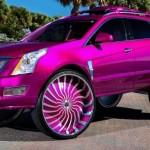 Růžový Cadillac SRX na obřích kolech